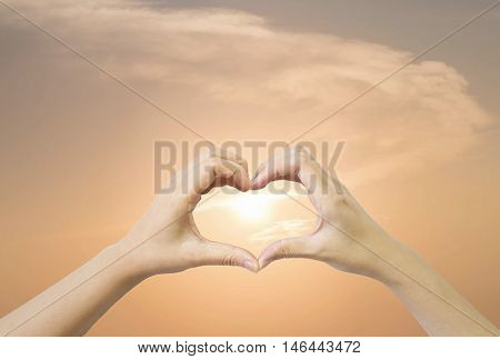 Closeup heart shape by two woman hand on evening sky with sunset background