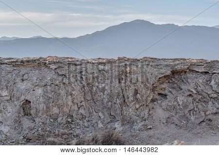 Stark Stone Wall: a stark, jagged stone wall, with a mountain in the background, at dusk