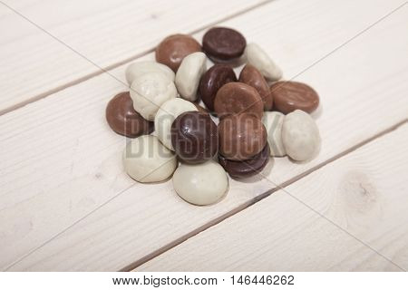 Pile of Dutch candy chocolate pepernoten on white wooden background