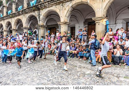 Antigua Guatemala - September 14 2015: Locals run by city hall with lit torches during Guatemalan Independence Day celebrations