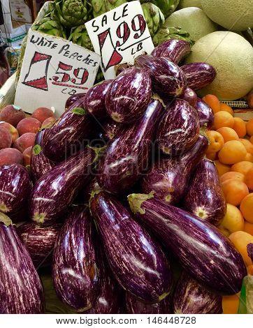 Beautiful Eggplant, Artichokes, Peaches, and Cantaloupe at farmer's market.