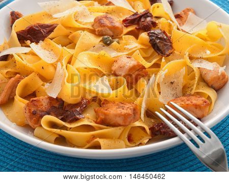 Italian Pasta - fettuccine with dried tomatoes baked salmon and parmesan cheese. Horizontal shot