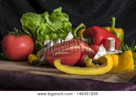 Colorful mix of fruits and vegetables on black velvet background