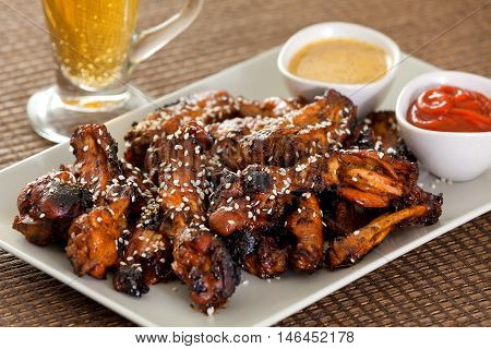 Baked chicken wings with barbecue sauce sesame seeds mustard and catchup. Beer on background