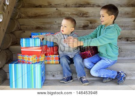kids pull hands to gifts. two boys excited getting gifts for the holiday. the concept of happy holidays. Christmas.