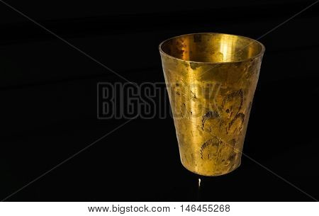 Antique copper cup on a black background