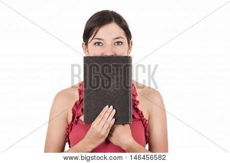 beautiful young female teacher covering face with book isolated on white