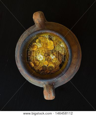 Fake gold and silver coins in earthenware jar