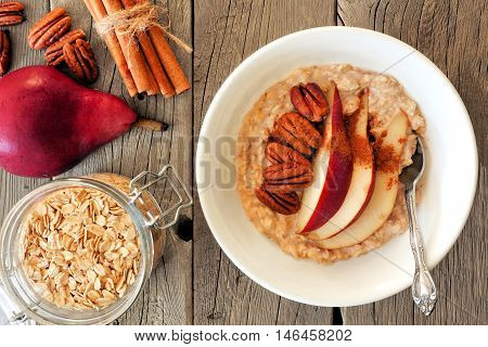 Autumn Breakfast Oatmeal With Red Pear, Pecans And Cinnamon, Overhead Scene On Rustic Wood