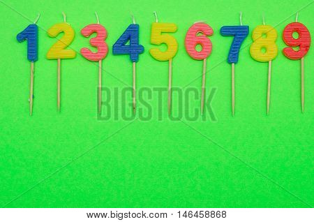 Birthday candles numbers 1 to 9 isolated on a green background