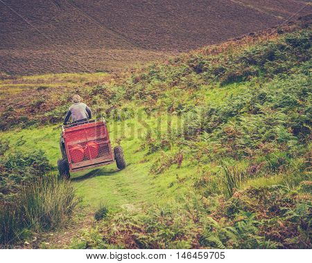 A Hill Farmer On A Quad Bike With Trailer In Rural Scotland