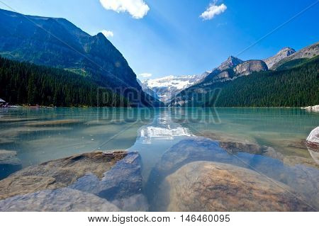 Beautiful alpine lake with reflections and rocks. Lake Louise.  Banff National Park. Rocky Mountains. Alberta. Canada.