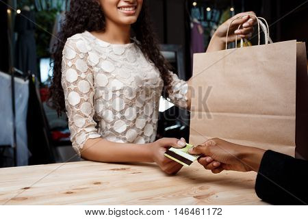 Close up photo of young beautiful african girl paying for buyings, smiling in shopping mall.