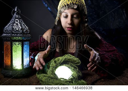 Woman dressed in a Halloween costume looking into a crystal ball