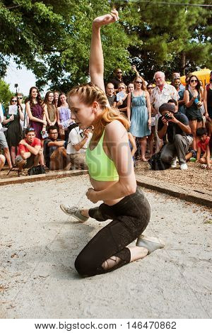 ATLANTA, GA - AUGUST 2016: A young female dancer with the Atlanta Ballet puts on a Wabi Sabi dance performance for the general public at a spot along the Atlanta Beltline Greenspace in Atlanta GA, on August 6 2016 .