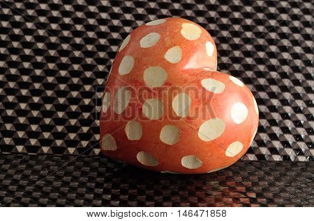 Valentine's day. A spotted red and white heart isolated on a black background