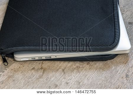Laptop in black soft case on wooden table