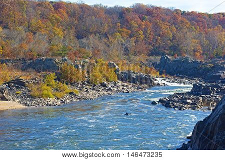 Potomac River flow after the waterfall in Great Falls state park Virginia USA. Fall forest landscape with road alongside the river.
