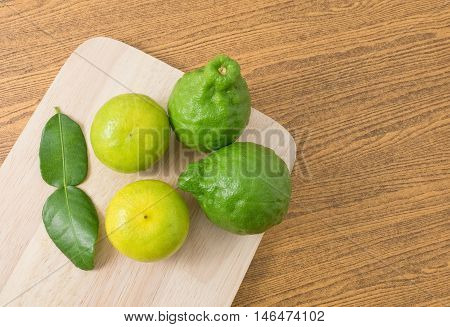 Vegetable and Herb Top View of Fresh Green Kaffir Lime with Persian Lime and Kaffir Leaves for Seasoning in Cooking on A Wooden Board with Copy Space for Text Decorated.