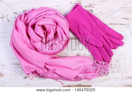 Woolen Gloves And Shawl For Woman On Old Wooden Background