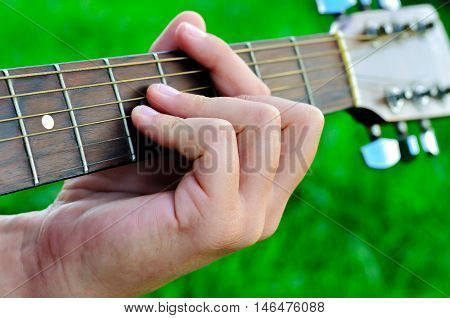 Man's hand and guitar strings close up