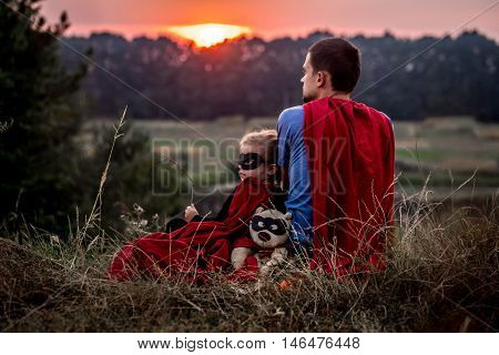 little girl with dad dressed in super heroes happy loving family father and daughter playing outdoors family values
