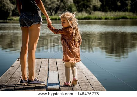 the daughter of a mother hold the hand on the pier at the lake