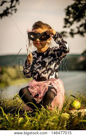 little girl playing on the grass in the daytime, the emotions of a child, a beautiful natural backdrop, playing with a mask