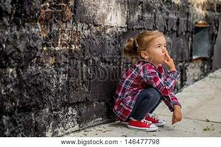 llittle beautiful girl near brick wall with red sneakers and a plaid shirt emotion girl