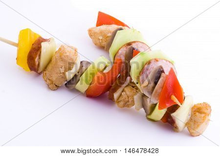Two chicken and vegetable kebabs, isolated on white.