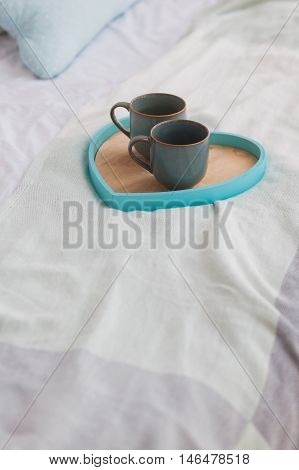Two blue mugs on a tray white bed, breakfast concept