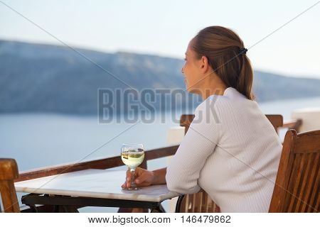 Woman with white wine in Oia Santorini. Looking at the caldera. Side view