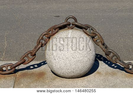 Ball of stone and on top is an iron chain.