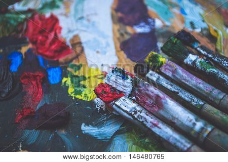Old palette, oil paints and painting brushes