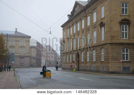 COPENHAGEN, DENMARK - NOVEMBER 01, 2014: The Postman on a city street a foggy november morning. Tourist landmark of the city Copenhagen