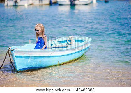 Little girl in Traditional fishing boat in Mykonos port, Mykonos island, Greece