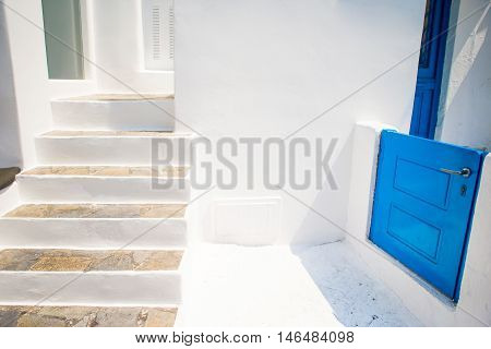 Typical staircase and a small door on the cozy streets of Mykonos, Cyclades.