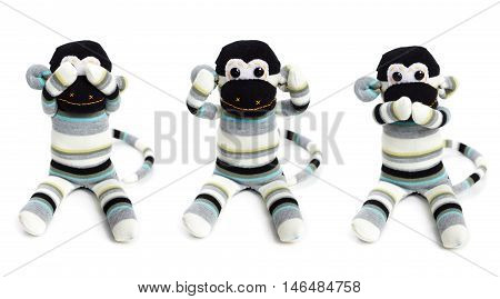 Three toy monkeys isolated on white background with hands on eyes ears and mouth