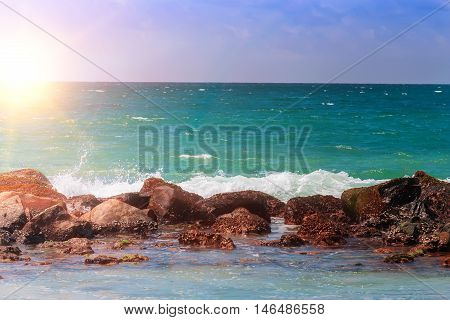 Turquoise ocean water blue sky and boulders on the beach paradise in the rays of the rising sun