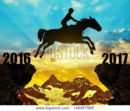 The rider on the horse jumping into the New Year 2017 at sunset