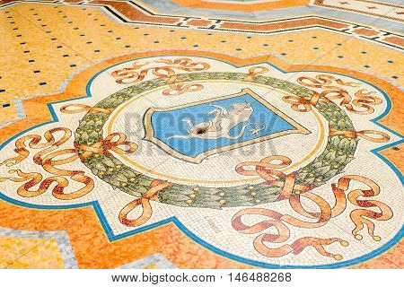 Milan, Italy - June 06, 2016: Famous mosaic bull on the floor of Vittorio Emanuele shopping gallery in Milan.