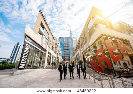 Milan, Italy - June 07, 2016: Businessmen walk on Vincenzo Capelli street with shopping boutiques and offices in Porta Nuova business district in Milan in the morning