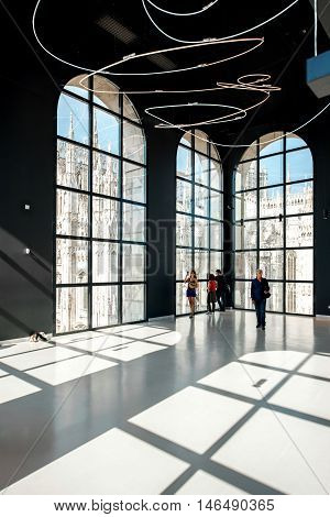 Milan, Italy - June 07, 2016: Big hall with visitors and great view on Duomo cathedral in Novecento museum. Novecento is a museum of twentieth-century modern art in Milan, opened in December 2010