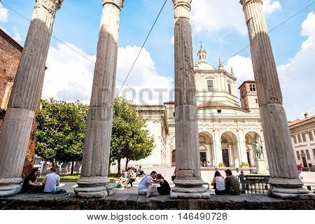 Milan, Italy - June 07, 2016: Street view with San Lorenzo Maggiore basilica and people sit and rest near the columns in Milan city.