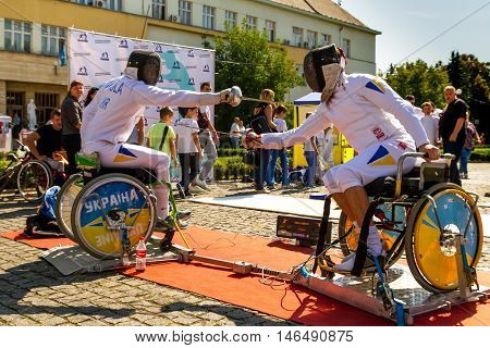 Uzhhorod Ukraine - September 9. 2016: Athletes sitting in wheelchair demonstrate their skills of fencing during the celebration of the Physical Culture and Sports Day. Similar events are held on this day in all cities of Ukraine.