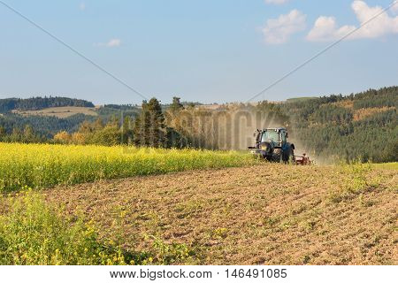 Blue tractor in a field of mustard in the Czech Republic. Dusty field and agricultural work. Autumn farm chores. The tractor mows mustard on a sunny day. Farmer working in the field.