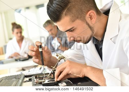 Student in technology fixing computer processing