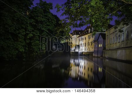Traditional view on the mill wheel on Certovka stream on Vltava river Prague Czech republic. Night picture with lights reflections in the water.