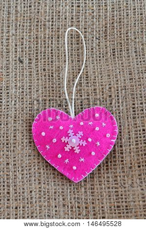 Pink felt heart embellished with beads and snowflake. Christmas tree ornament. Valentine's day symbol
