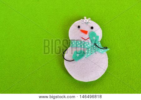 Christmas tree snowman ornament. Funny snowman toy is sewn of felt. Christmas background